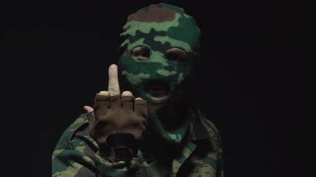 without face : Soldier in camouflage and military mask showing middle finger at camera