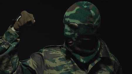 without face : Soldier in camouflage and military mask showing the strength of his biceps