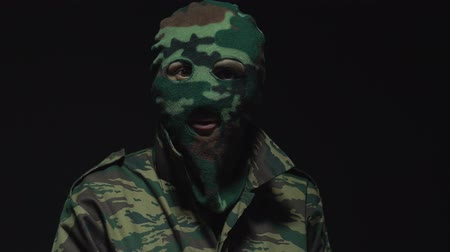 balaclava : Soldier in camouflage and military mask showing gesture that watches you Stock Footage