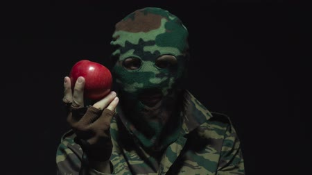 balaclava : Soldier in camouflage and military mask holding red apple