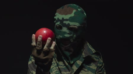 without face : Soldier in camouflage and military mask looking at red apple