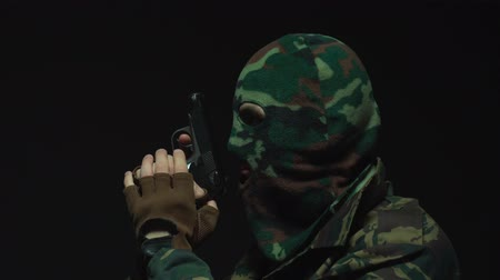 guarda costas : Side view of soldier in camouflage and military mask holding gun against an black background