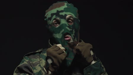 without face : Soldier in camouflage put on his military mask
