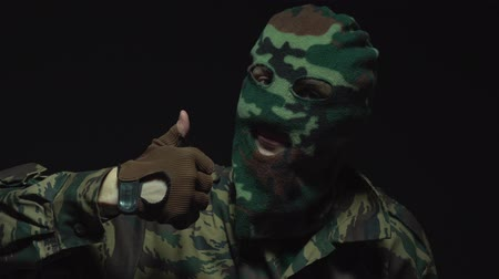 герой : Soldier in camouflage and a military mask showing thumbs up over black background