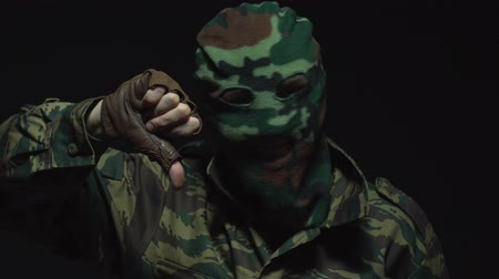 sem camisa : Soldier in camouflage and a military mask shows a thumb down to the camera