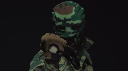 ameaça : The portrait the soldier in camouflage and military mask is threatens with a fist.