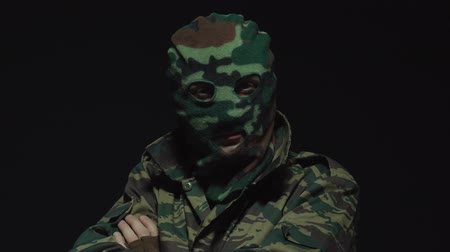 crossed : Soldier in camouflage and military mask looking at camera on black background