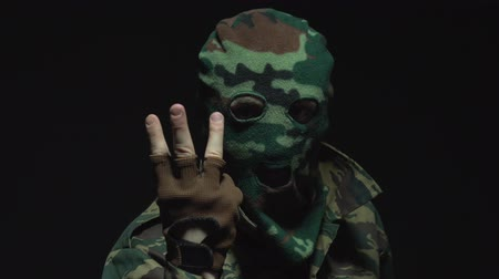 without face : A soldier in camouflage counting to three