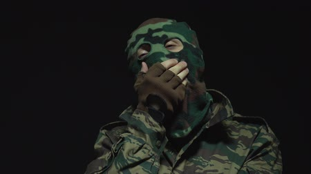 without face : Soldier in camouflage and military mask yawning on black background Stock Footage