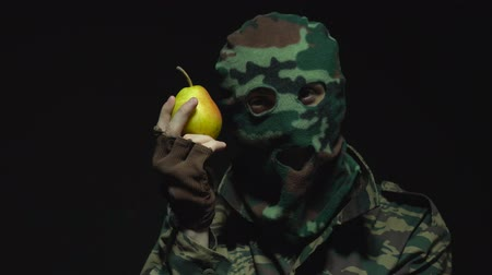 without face : Soldier in camouflage and military mask is sniffing a pear