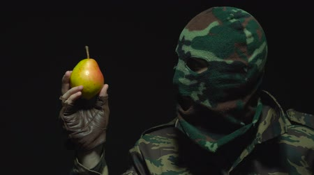 груша : Soldier in camouflage and a military mask is holding pear Стоковые видеозаписи