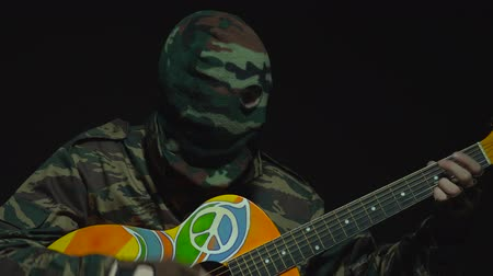 without face : Soldier in camouflage and a military mask is playing hippie guitar Stock Footage