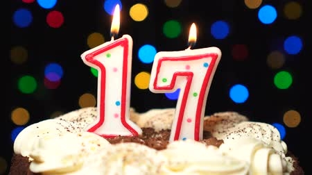 konfetti : Number 17 on top of cake - seventeen birthday candle burning - blow out at the end. Color blurred background Wideo
