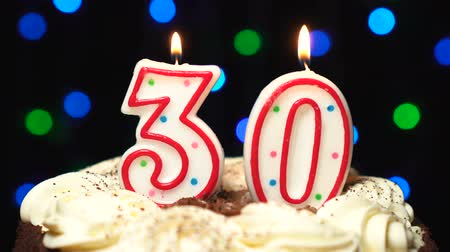 otuzlu yıllar : Number 30 on top of cake - thirty birthday candle burning - blow out at the end. Color blurred background