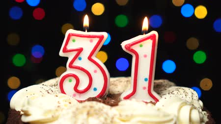 otuzlu yıllar : Number 31 on top of cake - thirty one birthday candle burning - blow out at the end. Color blurred background