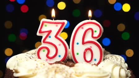 otuzlu yıllar : Number 36 on top of cake - thirty six birthday candle burning - blow out at the end. Color blurred background