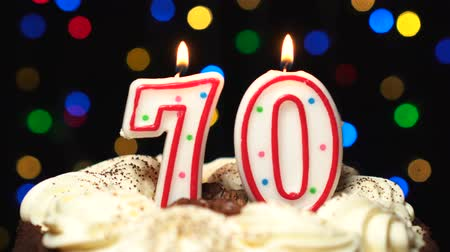 gênero alimentício : Number 70 on top of cake - seventy birthday candle burning - blow out at the end. Color blurred background Stock Footage