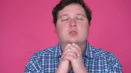 thick : Young man praying on pink studio background