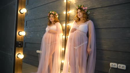 mama : Pregnant woman in pink peignoir stands near mirror. She put hand on her belly