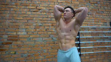 üstsüz : Bodybuilder posing in gym on background of bricks wall