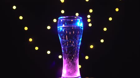 combinado : Glass of water in pink-blue light is spinning. Pink-blue cocktail. Bar concept Vídeos