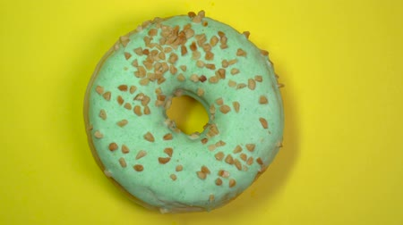 doughnut : Delicious sweet donut quickly rotating on a plate. Top view. Yellow background.