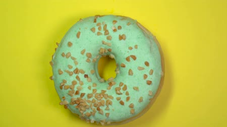 окропляет : Tasty sweet green donut rotating on a plate. Top view.
