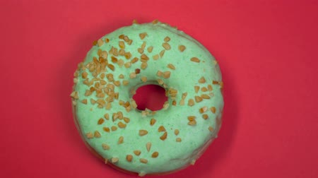 envidraçado : Tasty sweet donut rotating on a plate. Top view.