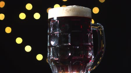 frothy : A pint of dark beer foam beautifully against black background