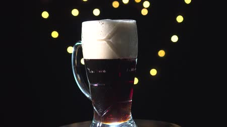 пивоваренный завод : Beer is pouring into the mug. Stout beer mug is spinning