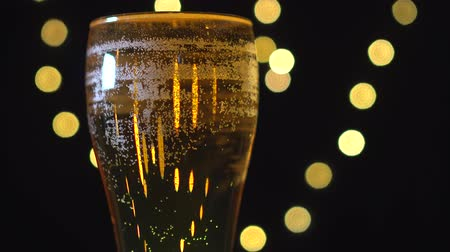 lights up : Delicious golden beer in a glass is spinning on background of blurred lights.