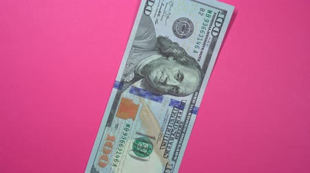 cem : One hundred dollars fast spinning on a rotating pink background.