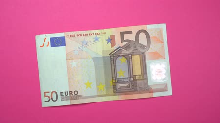 euro banknotes : 50 euro slowly spinning on a rotating pink background. Stock Footage