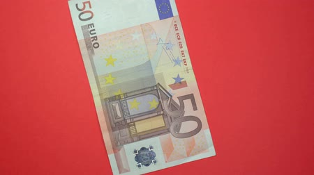 eur : 50 euro fast spinning on a rotating red background.