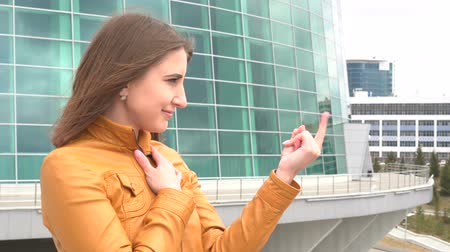 beckoning : Very beautiful girl is inviting to come at camera outdoor in the city. Stock Footage