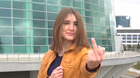 transação : Very beautiful girl makes obscene hand gesture by showing middle finger in the city outdoor.