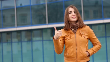 human like : Beautiful young caucasian woman smiling with thumb up outdoor in the city.