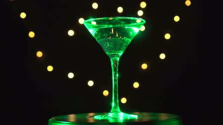 vermouth : Bright cocktail in glass, spinning and change colours on dark background with blurred light. Stock Footage