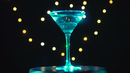 vermouth : Bright cyan cocktail in glass, spinning on dark background with blurred light.