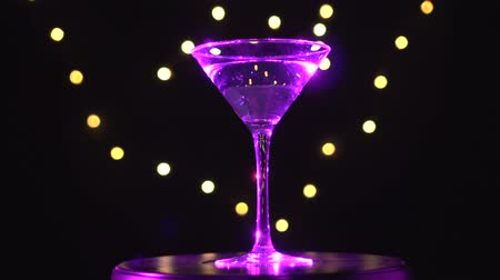 vermouth : Bright magenta cocktail in glass, spinning on dark background with blurred light. Stock Footage