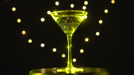 vermouth : Bright yellow cocktail in glass, spinning on dark background with blurred light.
