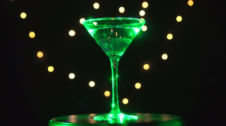 vermouth : Bright green cocktail in glass, spinning on dark background with blurred light.