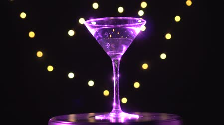 vermouth : Bright pink cocktail in glass, spinning on dark background with blurred light.