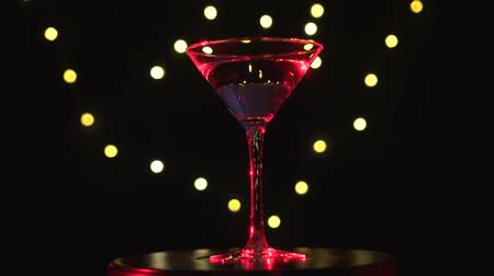 vermouth : Bright red cocktail in glass, spinning on dark background with blurred light.