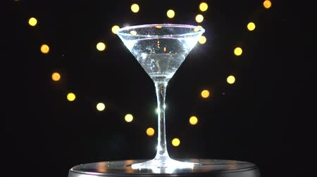 vermouth : Bright white cocktail in glass, spinning on dark background with blurred light. Stock Footage