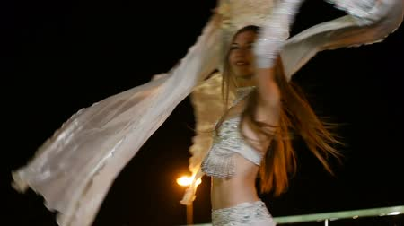 vytržení : Beautiful young woman in oriental ethnic costume dances at night outdoor