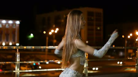держит : Beautiful young woman in oriental ethnic costume dances at night outdoor