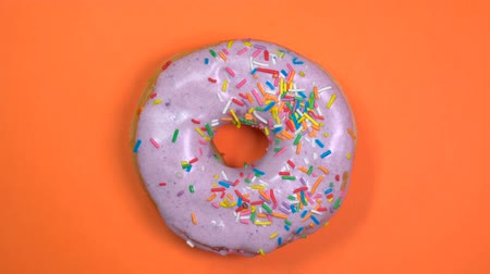 mázas : Bright and colorful sprinkles donut, macro shot, fast spinning on a plate on a orange background.