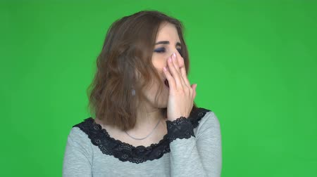 can sıkıntısı : Tired young woman yawns and covering her mouth while looking at the camera over green background.