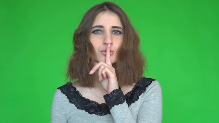 looking for : Silence, please! Portrait of young woman holding her forefinger on lips showing hush silence sign Stock Footage